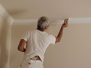 The painter applies a final coat to the crown molding.
