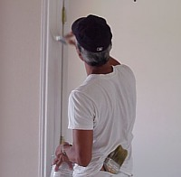 A workman applies a second coat of paint to the door frame.